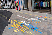 A construction workman and multi-coloured aerosol-sprayed markings on the ground, in a side-street off Long Acre near Covent Garden, are on 23rd June 2021, in Westminster, London, England.