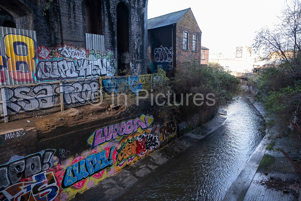 Street art along the River Rea in the old industrial area and railway arches of Digbeth on 14th December 2020 in Birmingham, United Kingdom. Following the destruction of the Inner Ring Road, Digbeth is now considered a district within Birmingham City Centre, and is the epicentre for arts and graffiti artworks as well as its status as a once-gritty bohemian district known for street art and a young and hip people attending events and creative workshops at the Custard Factory and grungy clubs in former warehouses. As part of the Big City Plan, Digbeth is undergoing a large redevelopment scheme that will regenerate the old industrial buildings into apartments, retail premises, offices and arts facilities. There is still however much industrial activity in the south of the area.