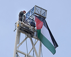 © Licensed to London News Pictures. 15/06/2021. London, UK .A police cordon ands road closures are in place on Nine Elms Lane after a man climbed to the top of a crane on a building site that is close to the U.S. Embassy. The man has hung a Palestinian flag from the top of the crane. Photo credit: George Cracknell Wright/LNP