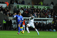 Wilfried Bony of Swansea city ® breaks past Everton's Sylvain Distin. Barclays Premier league, Swansea city v Everton at the Liberty Stadium in Swansea,  South Wales on Sunday 22nd Dec 2013. pic by Andrew Orchard, Andrew Orchard sports photography.