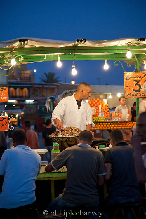A man selling escargot, cooked snails, at a stall in the Djemaa el Fna in the medina of Marrakech, Morocco. Every night the main square fills with dozens of food vendors and their carts.