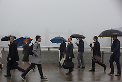 © Licensed to London News Pictures. 11/05/2016. LONDON, UK.  Early morning commuters cross London Bridge in London during foggy and wet weather this morning.  The normally visible Tower Bridge in the background has almost disappeared into the fog. Photo credit: Vickie Flores/LNP