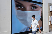 Picture of a model wearing a face mask adorns an advertisement for medical premises in Marylebone on 10th August 2021 in London, United Kingdom. Passing people interract with the large scale photo poster of a woman with beautiful eyes looking out from above her face covering, which has direct connotations during these times where coronavirus / Covid-19 affects daily life.