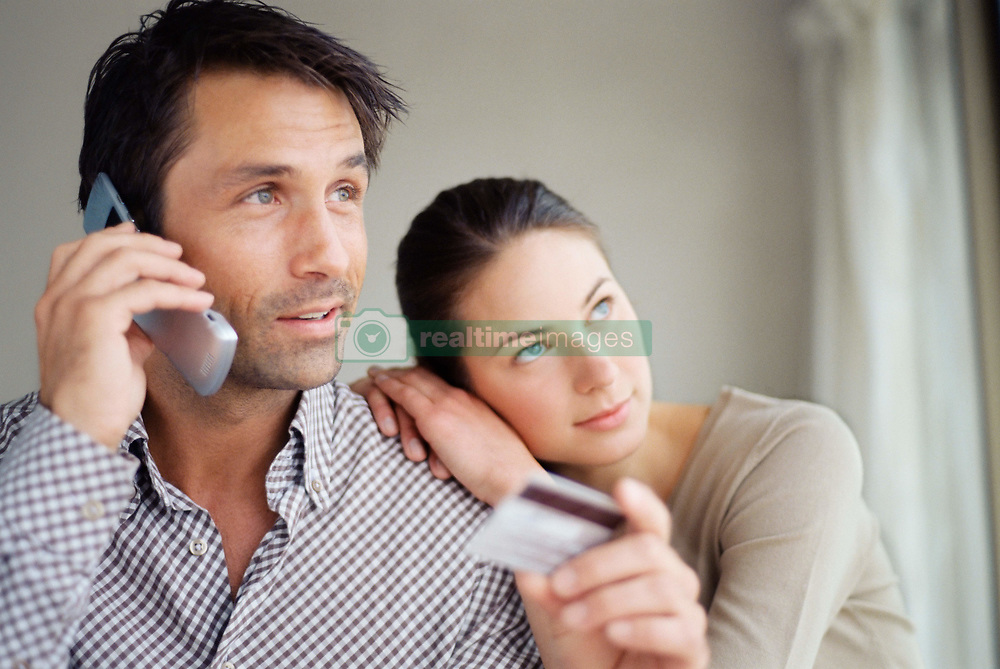 Dec. 14, 2012 - Couple using credit card over the telephone (Credit Image: © Image Source/ZUMAPRESS.com)