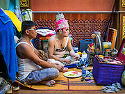 "30 JANUARY 2016 - NONTHABURI, NONTHABURI, THAILAND: Members of a ""likay"" troupe snack and watch the ""likay"" show at Wat Bua Khwan in Nonthaburi, north of Bangkok. Likay is a form of popular folk theatre that includes exposition, singing and dancing in Thailand. It uses a combination of extravagant costumes and minimally equipped stages. Intentionally vague storylines means performances rely on actors' skills of improvisation. Like better the known Chinese Opera, which it resembles, Likay is performed mostly at temple fairs and privately sponsored events, especially in rural areas. Likay operas are televised and there is a market for bootleg likay videos and live performance of likay is becoming more rare.     PHOTO BY JACK KURTZ"