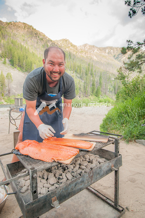 Guide smiles while cooking Cedar plank salmon dinner at Sheepeater Camp, Middle Fork of the Salmon River, Idaho.