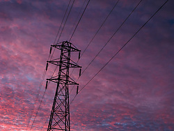 Pink cloudy evening sky with power lines and tower