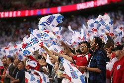 England fans wave three lions flags in the stands