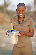 Local staff serve champagne chilled in an ice bucket at Abu Camp, a luxury safari camp in the Okavango Delta, Botswana