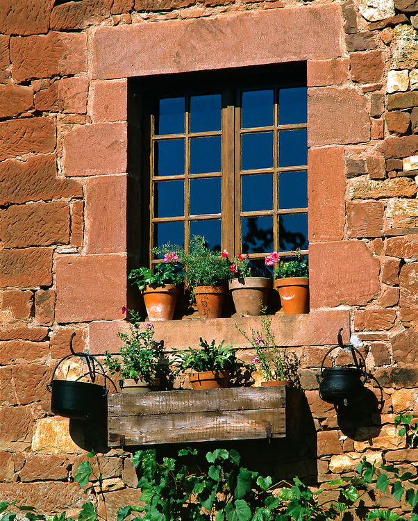 Colorful flower pots adorn a window in this home in Collognes-la-Rouge in the Dordogne, France.