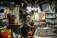 An elderly seller sits in her crowded stall in a market in Dong Da District, Hanoi, Vietnam, Southeast Asia