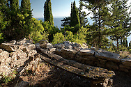A viewing spot to the Aegean Sea through cypress trees and an old wooden seat on the Orkos Estate, Paxos, Greece, Europe