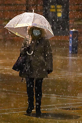 © Licensed to London News Pictures. 14/01/2021. Leeds, UK. A woman holds an umbrella as she walks in Leeds city centre during heavy snow this morning. Photo credit: Ioannis Alexopoulos/LNP