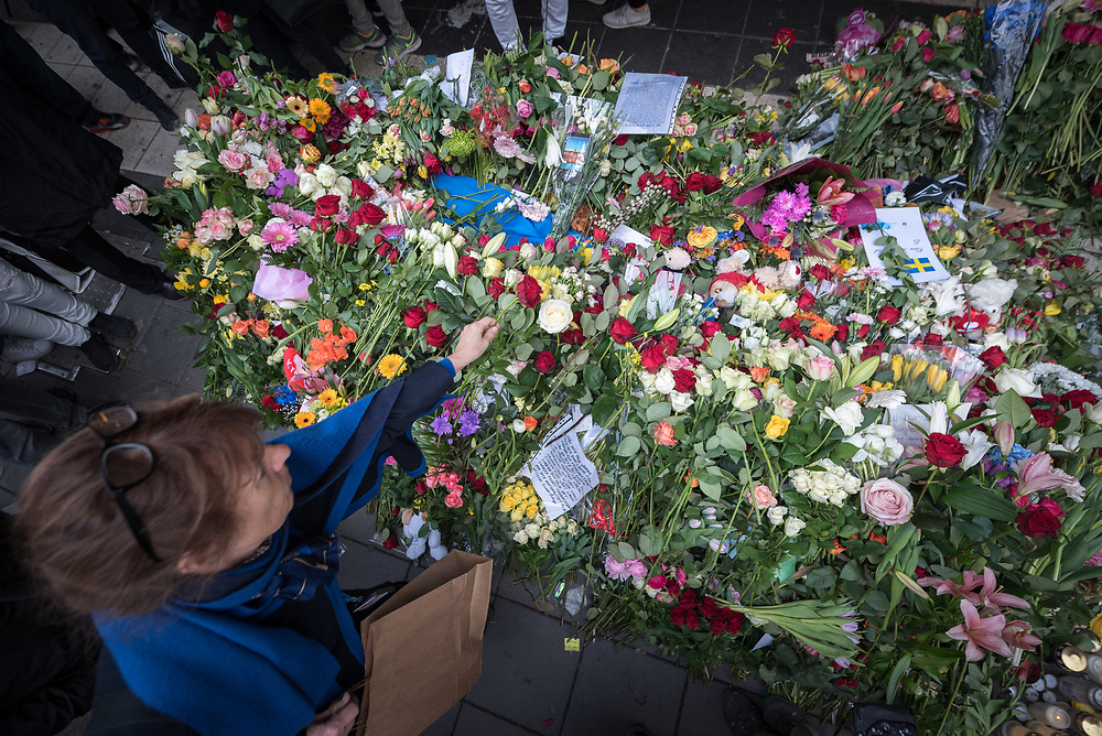 10 April 2017, Stockholm, Sweden: Commemoration of the victims of terror, on Drottninggatan (Queen Street) in central Stockholm, three days after a lorry was driven into a store in central Stockholm, killing at least four people and injuring many more. Here, Lotta Cronsioe places a red rose onto a bed of flowers commemorating the victims of the attack. Oral consent obtained for use by Church of Sweden and the World Council of Churches.