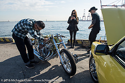 Kiyo Mitsuhiro of Kiyo's Garage in Gardenam, CA, with his wife Kat and Ryan Grossman in the background, ready to light up his twin-4-cylinder Honda drag bike at the Yokohama docks where the invited custom builder's bikes from the USA were unloaded prior to the Mooneyes Yokohama Hot Rod & Custom Show. Yokohama, Japan. December 3, 2016.  Photography ©2016 Michael Lichter.