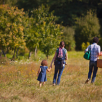 A family walks out to a meadow at Zenger Farms in Portland, Oregon to have a picnic.