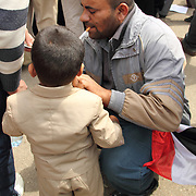 A proud father helps his son with his suit in Tahrir Square, Cairo.