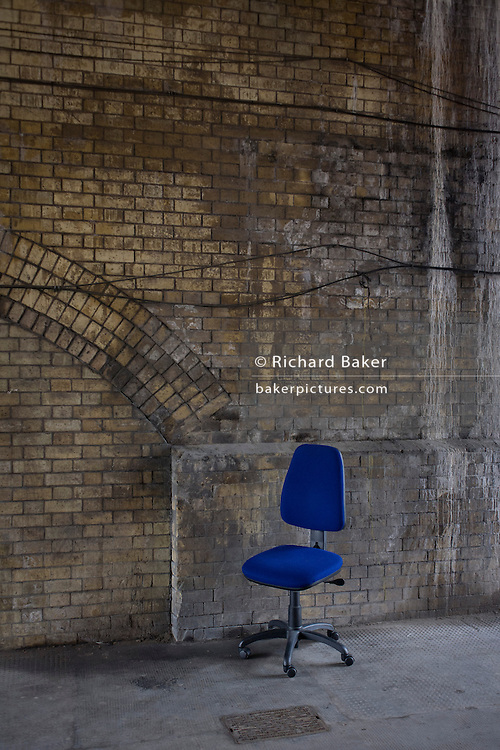 A bright, new blue office chair incongruously left in a street with stained Victorian brickwork of a tunnel, in the London district of Clerkenwell. Set against the poverty of the road arch brick, we see contemporary modern office furniture and a previous 19th century era.
