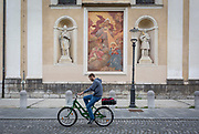 While checking his phone, a cyclist rides past a mural and sculpture outside Cathedral of saint Nicholas in the Slovenian capital, Ljubljana, on 28th June 2018, in Ljubljana, Slovenia. Ljubljana is a small city with flat terrain and a good cycling infrastructure. It was featured at eighth on the 'Copenhagenize' index listing the most bike-friendly cities in the world though bike theft is prevalent.