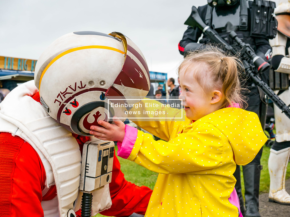Pictured: Scotland's National Airshow, East Fortune, East Lothian, Scotland, United Kingdom, 27 July 2019 . A packed programme of aircraft old and new planned to take to the skies for the aerial display was marred by poor weather at airfields around the country which meant that many of the promised flights were unable to perform. A liitle girl, Isla, is delighted by the Stormtroopers.<br /> Sally Anderson | EdinburghElitemedia.co.uk