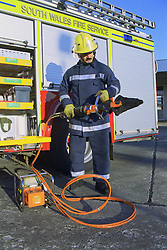 Part time male firefighter standing in front of fire engine checking cutting equipment,