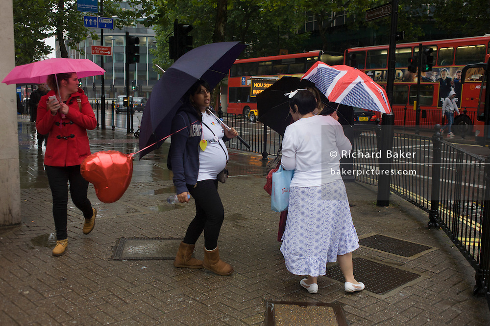 Women, incl one pregnant with a heart-shaped balloon, on a street corner shelter under umbrellas during damp, gloomy weather in central London.