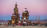 The Folly by: Dave Keane & The Folly Builders from: San Francisco, CA year: 2019 The Folly represents an imaginary shantytown of funky climbable towers and old western storefronts, cobbled together from salvaged and reclaimed lumber from original San Francisco Victorians to be reborn in the desert, affording shelter, entertainment and perspective to the community. URL: www.thefollybrc.com Contact: info@thefollybrc.com https://burningman.org/event/brc/2019-art-installations/?yyyy=&artType=H#a2I0V000001AVkAUAW