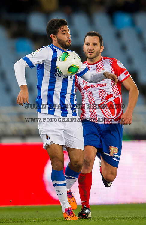 SAN SEBASTIAN, SPAIN - DECEMBER 18:  Carlos Vela ofÊReal Sociedad duels for the ball with Merino of Algeciras CF during the Copa del Rey Round of 32 match betweenÊReal Sociedad and Algeciras CF at Estadio Anoeta on December 18, 2013 in San Sebastian, Spain.Ê (Photo by Juan Manuel Serrano Arce/Getty Images)Ê
