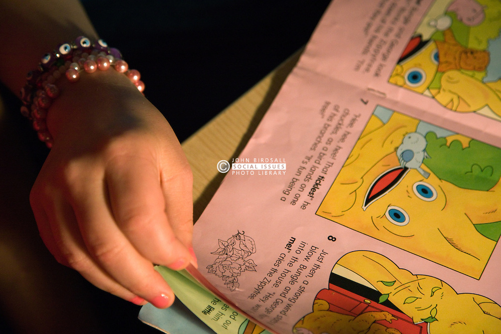 Day Service user with learning disability turning the page of a story book,