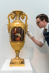 "© Licensed to London News Pictures. 31/05/2019. LONDON, UK. A technician examines ""A monumental porcelain vase"", made in the Imperial Porcelain Factory, St Petersburg"", 1857, (Est. GBP 200,000-300,000) at a preview of works from the upcoming sale of Russian Pictures, Works of Art, Fabergé & Icons Sales at Sotheby's, New Bond Street, on 4 June 2019.  Photo credit: Stephen Chung/LNP"