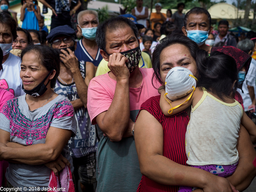 24 JANUARY 2018 - GUINOBATAN, ALBAY, PHILIPPINES: People evacuated from the slopes of the volcano, listen to Leni Robredo, the Vice President of the Philippines, speak to them at Barangay Maninila Evacuation Center in Guinobatan East Central School.  The Mayon volcano continued to erupt Tuesday night and Wednesday forcing the Albay provincial government to order more evacuations. By Wednesday evening (Philippine time) more than 60,000 people had been evacuated from communities around the volcano to shelters outside of the 8 kilometer danger zone. Additionally, ash falls continued to disrupt life beyond the danger zones. Several airports in the region, including the airport in Legazpi, the busiest airport in the region, are closed indefinitely because of the amount of ash the volcano has thrown into the air.    PHOTO BY JACK KURTZ