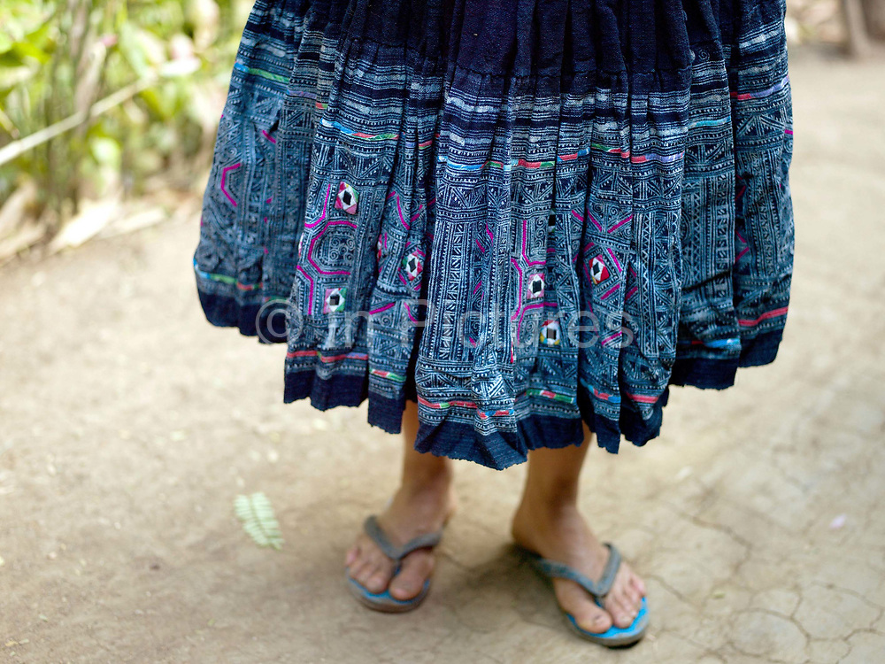 Yua, a Hmong Du woman wears her traditional skirt made from hand woven hemp (cannabis sativa), decorated with batik (a wax resist technique) and dyed with indigo, Ban Vieng Hang, Houaphan province, Lao PDR. The batik motif is the basis for hand stitched cotton appliqué and embroidery. Making hemp fabric is a long and laborious process; the end result is a strong durable cloth with qualities similar to linen which the Hmong Du women make into skirts, for their traditional clothing. In Lao PDR, hemp is now only cultivated in remote mountainous areas of the north.