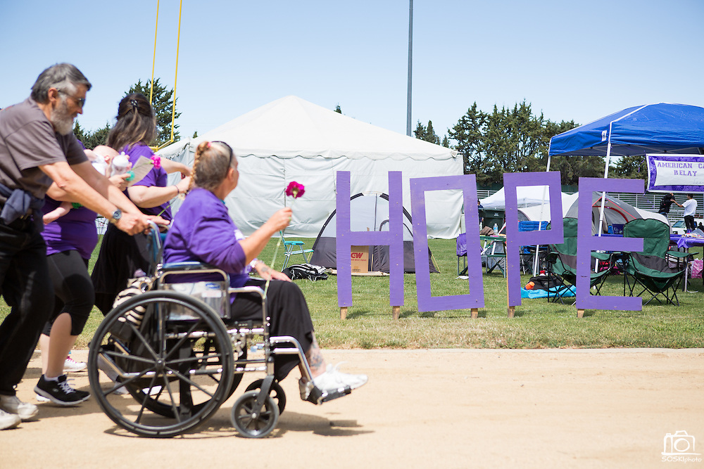 Jennifer Cole, survivor of colon cancer, and caregiver Al Newman pass the HOPE sign near the American Cancer Society booth during the opening lap of Relay For Life at the Milpitas Sports Center on June 23, 2012.  Photo by Stan Olszewski/SOSKIphoto.