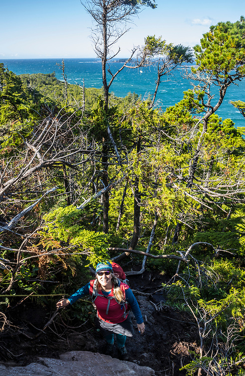 A woman atop Cox Bay Butte at the south end of Cox Bay Beach in Tofino, BC, Canada.