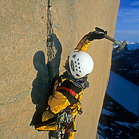 3,000 feet above the ground on a huge, overhanging granite cliff - the northernmost big wall climb yet attempted at the time - mountaineer Greg Child pounds a piton into a thin crack that is the only route upwards.  He is lit by frigid midnight sun, north of the Arctic Circle, and progress was so slow that the team required nearly a month to complete the route.