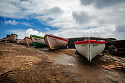 row of colorful fishing boats under pale sky in Sao Miguel, Azores
