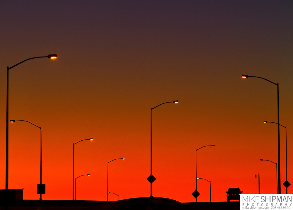 An SUV drives on the highway silhouetted at Sunset in, Boise, Idaho, USA