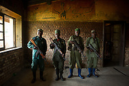 CLIENT: WILD EARTH ALLIES<br /> <br /> Left to right, park rangers Prince Makanda, Augustin Kafunzi, Mubila Kitungano, and Mirindi Bashizi, inside of the Tshibati ranger outpost just outside of Kahuzi-Biega National Park in Lwiro, South Kivu, D.R. Congo. The building, once part of an experimental zoological farm developed by the Belgians in the 1950's, has been used by various arms of the military in recent years, and is now barracks for the rangers. Graffiti on the wall depicts fighter planes, helicopters, bombs and other weapons of war.