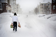 A woman makes her way back to her apartment from the local grocery store during what is being called an epic snowfall in Northern Virginia and the D.C. metro area.