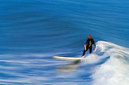 A surfer catches a wave in Santa Barbara, California.