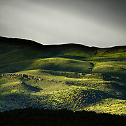 The sun breaks through a thunderstorm on the mountain sides above Eagle Colorado during spring greenery.