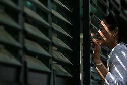12 July 2017 -  Wimbledon Tennis (Day 9) - A fan peers through the slatted wooden grille on court 18 - Photo: Marc Atkins / Offside.