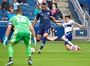 May 16, 2021 - Kansas City, KS, United States:  Sporting Kansas City forward Khiry Shelton (11, center) takes a shot on Vancouver Whitecaps goalkeeper Maxime Crepeau (16, left) as Vancouver Whitecaps defender Cristian Gutierrez (3) drops to the turf and tries to slide tackle the ball away.  Sporting KC beat the Vancouver Whitecaps FC 3-0 in a Major League Soccer game. <br /> Photo by Tim Vizer/Polaris