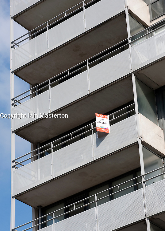 Modern apartment building with For Sale sign on balcony in The Hague, The Netherlands