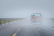 "A 1970's Ford F150 pickup travels through a storm on a remote section of US Highway 50, known as ""The Lonliest Highway in America,"" between Eureka and Austin, Nevada."