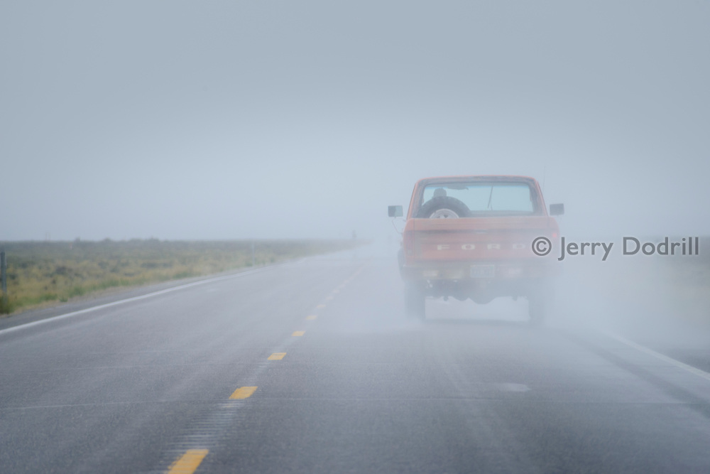 """A 1970's Ford F150 pickup travels through a storm on a remote section of US Highway 50, known as """"The Lonliest Highway in America,"""" between Eureka and Austin, Nevada."""