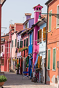 "Brightly painted blue, pink, red, and orange houses. Burano, known for knitted lacework, fishing, and colorfully painted houses, is a small archipelago of four islands linked by bridges in the Venetian Lagoon, in the Veneto region of Italy, Europe. Burano's traditional house colors are strictly regulated by government. The Romans may have been first to settle Burano. Romantic Venice (Venezia), ""City of Canals,"" stretches across 100+ small islands in the marshy Venetian Lagoon along the Adriatic Sea in northeast Italy, between the mouths of the Po and Piave Rivers. Venice and the Venetian Lagoon are honored on UNESCO's World Heritage List."