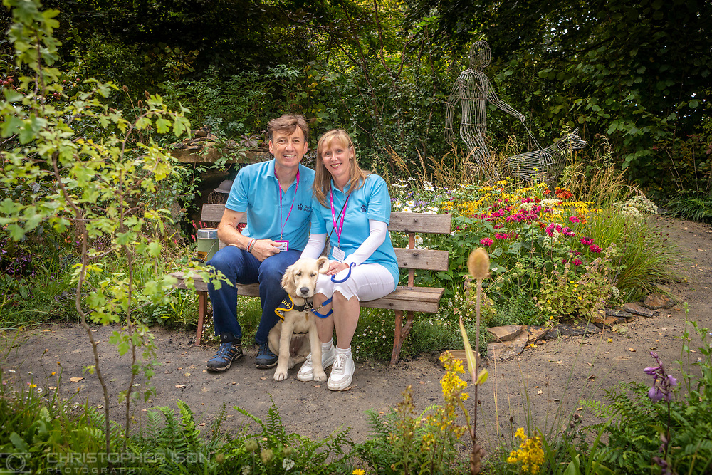 Guide Dog puppy in training, Chelsea, pictured in the Artisan Garden at RHS Chelsea with her puppy walkers Phil and Pat Bland. The garden has been created this year in celebration of 90 years of guide dog partnerships in Britain. Chelsea is 18 weeks-old and named to celebrate the event.<br /> Picture date: Monday September 20, 2021.<br /> Photograph by Christopher Ison ©<br /> 07544044177<br /> chris@christopherison.com<br /> www.christopherison.com