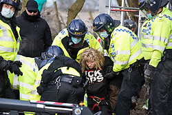 Steeple Claydon, UK. 24 February, 2021. Thames Valley Police officers arrest an activist opposed to the HS2 high-speed rail link after evicting him from ancient woodland known as Poors Piece. Thames Valley Police stepped in to replace National Eviction Team bailiffs. The activists created the Poors Piece Conservation Project in the woodland in spring 2020 after having been invited to stay on the land by its owner, farmer Clive Higgins.