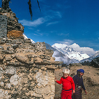 A Sherpani woman watches  3-year old Ben Wiltsie circle a Tibetan Buddhist chorten while trekking  in the Khumbu Region of Nepal, with Mounts  Everest &  Lhotse in background.
